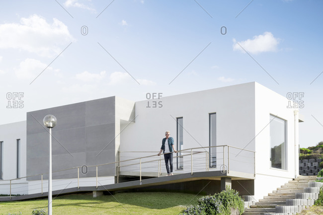 Casual man standing in front of his modern home