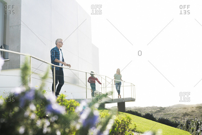 Casual man with his family standing in front of modern home looking at the landscape