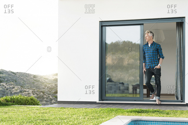 Casual man standing in front of his modern home with pool looking at the landscape