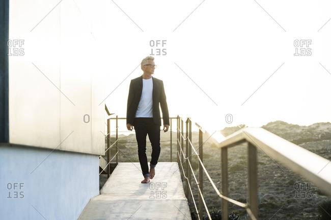 Businessman walking along his modern home looking around