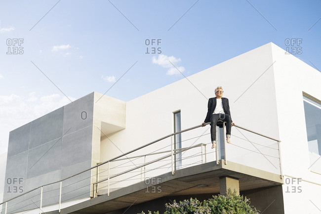 Businessman sitting on handrail in front of his modern house