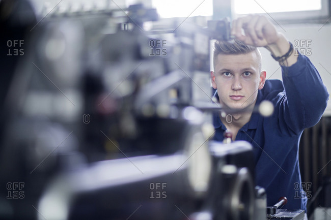 Young man adjusting a machine in a printing company