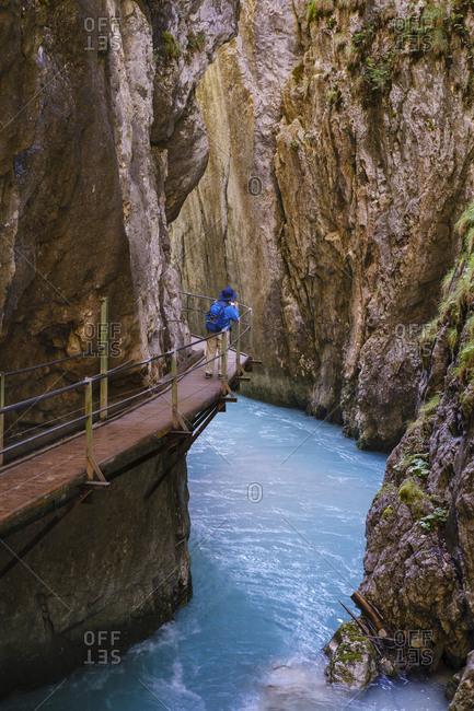 Senior woman on footbridge at Wasserfallsteig in Leutasch Gorge- Tyrol- Austria