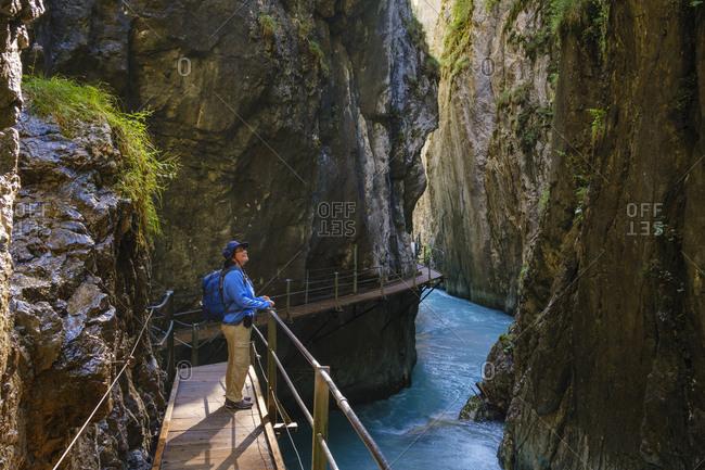 Side view of senior woman standing on footbridge at Wasserfallsteig in Leutasch Gorge- Tyrol- Austria