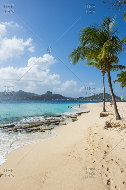 December 31, 2014: Scenic view of palm fringed white sand beach on Palm island with Union island in background- Grenadines islands- St. Vincent and the Grenadines- Caribbean