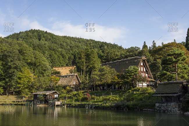 Japan- Takayama- Historical Hida Folk Village with forested hill in background