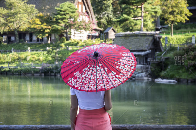 Japan- Takayama- Young woman holding pink traditional umbrella admiring historical Hida Folk Village