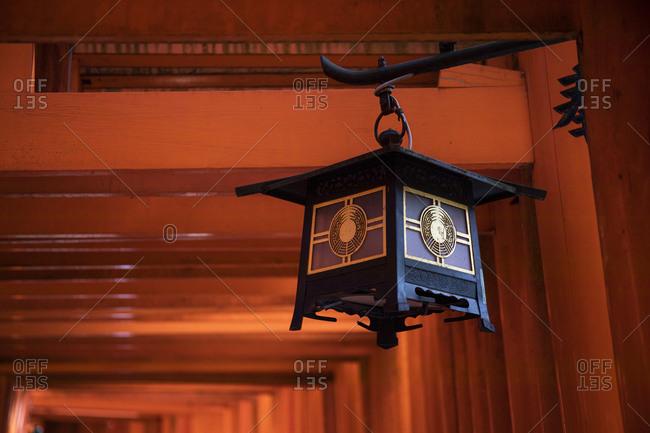 Japan- Kyoto Prefecture- Kyoto City- Lantern hanging under torii gate of Fushimi Inari-taisha temple