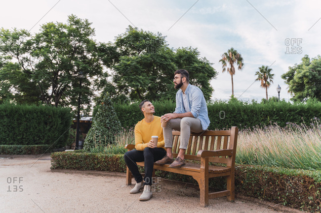 Gay couple relaxing with coffee to go on wooden bench in a park- Barcelona- Spain