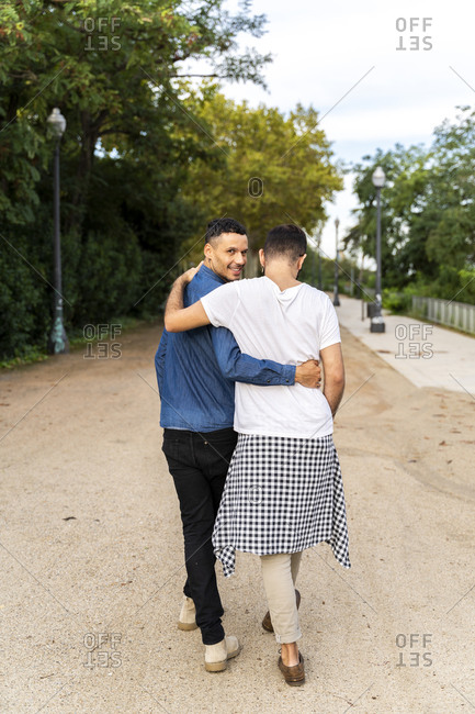 Back view of happy gay couple walking arm in arm in a park- Barcelona- Spain