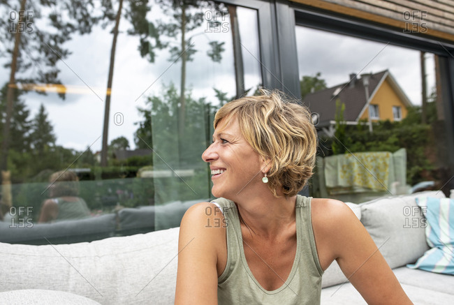 Happy woman relaxing on terrace at home