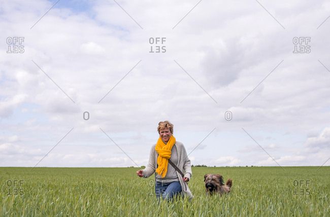 Happy woman going walkies with dog in a field