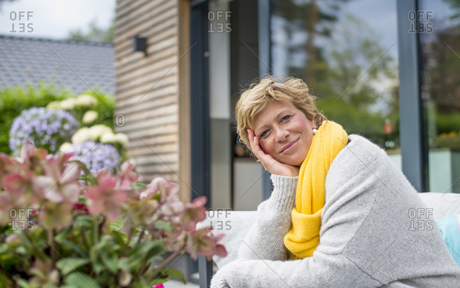 Portrait of smiling woman relaxing on terrace at home
