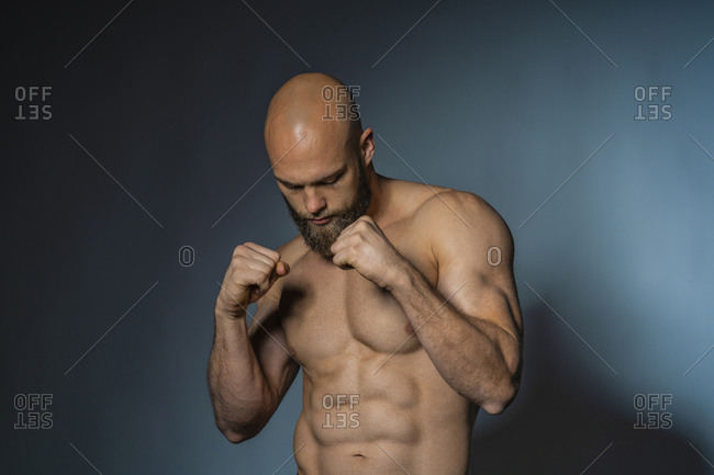 Barechested athlete in boxing pose in studio