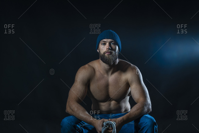 Portrait of a barechested athlete sitting in studio