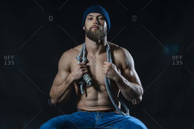 Portrait of a barechested athlete with skipping rope sitting in studio