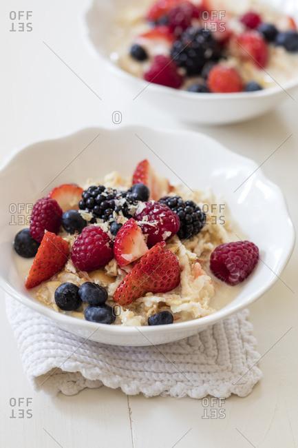 Bowls of fresh vegan muesli with various berries- currants and almond milk