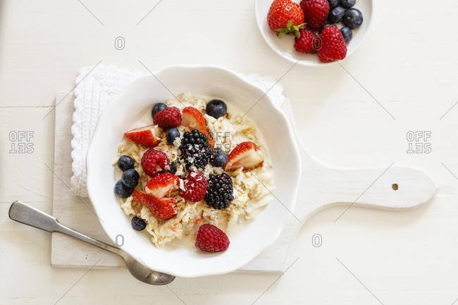 Bowl of fresh vegan muesli with various berries- currants and almond milk