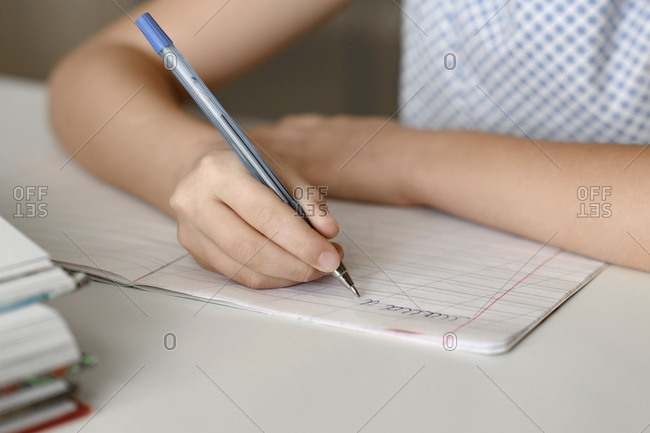Close-up of girl sitting at table at home writing in workbook