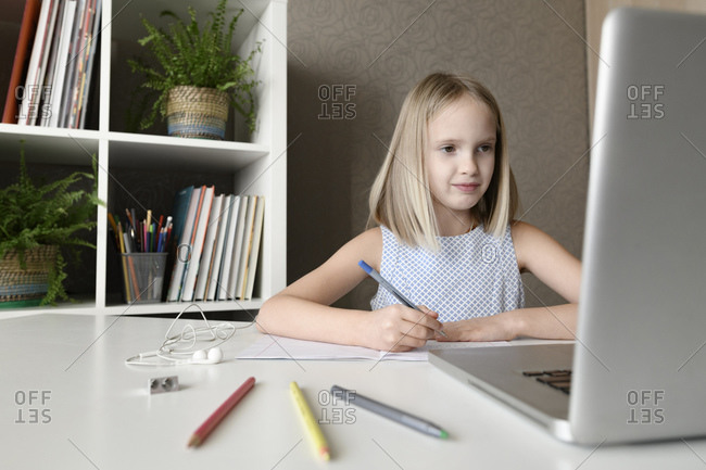 Girl sitting at table at home doing homework and using laptop