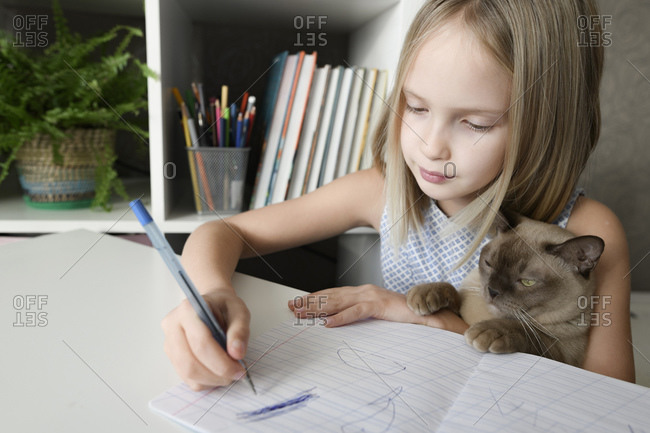 Girl with a cat sitting at table at home doing homework