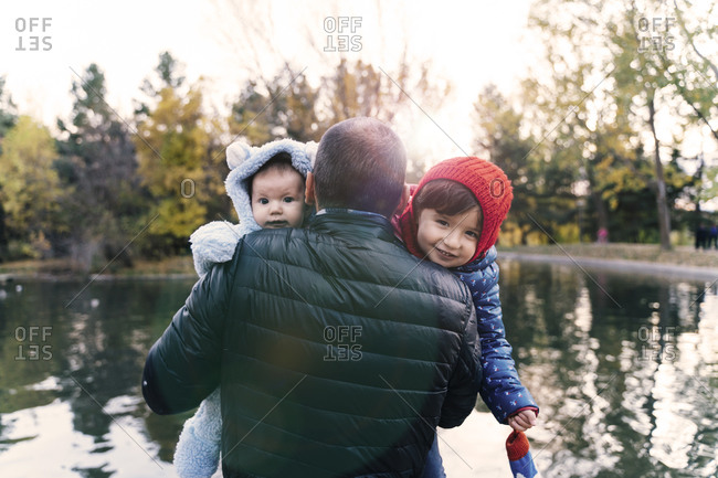 Portrait of two little girls on father's arms in front of a lake at sunset