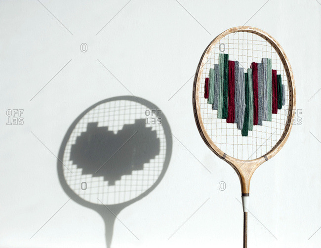 Badminton racket with wool heart and the shadow on the wall