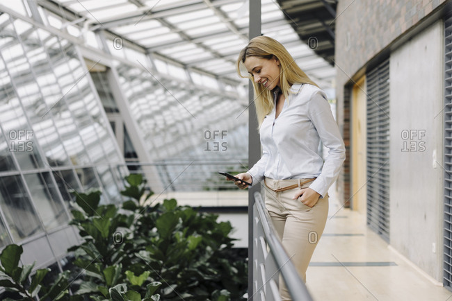 Smiling young businesswoman using cell phone in a modern office building