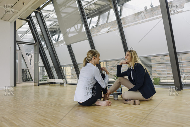 Two smiling young businesswomen sitting on the floor and talking in office