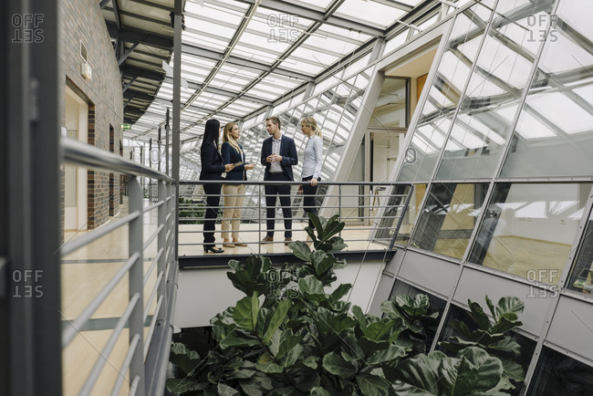 Business people standing on a skywalk in modern office building