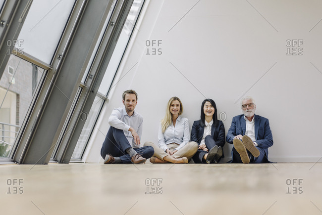 Portrait of smiling business people sitting on the floor in office