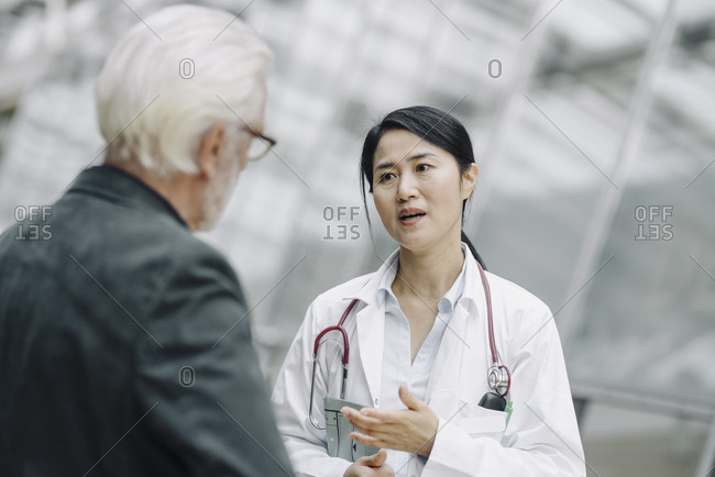 Female doctor talking to senior man