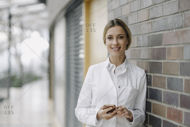 Portrait of a confident female doctor leaning against a brick wall