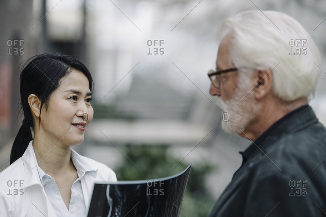 Smiling female doctor with x-ray and senior man talking