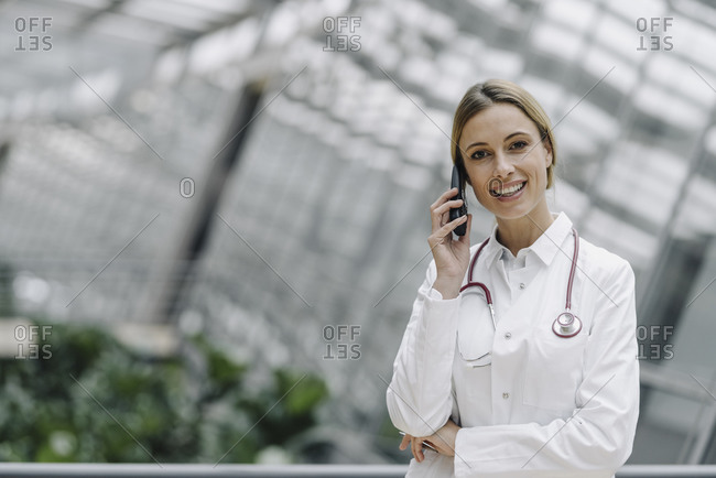 Portrait of a smiling female doctor on the phone