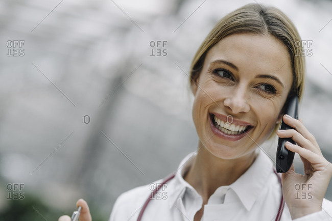 Portrait of a happy female doctor on the phone