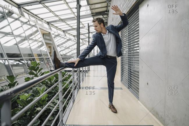 Businessman standing on one leg in modern office