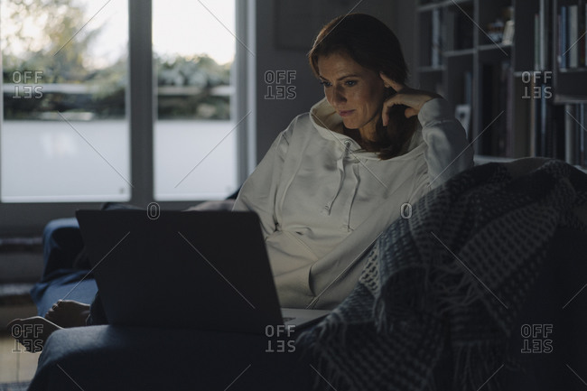 Woman sitting on couch of dark living room- using laptop