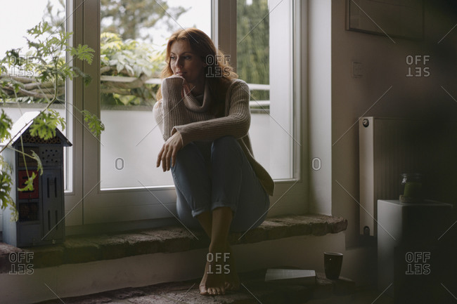 Mature woman sitting on steps of balcony door- daydreaming