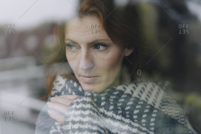 Woman looking out of window- wrapped in blanket