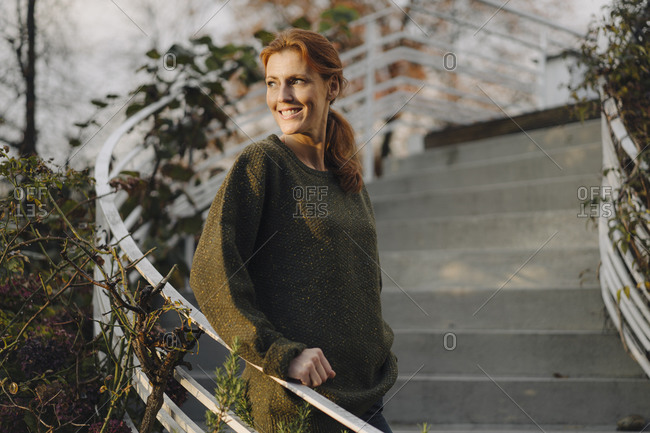 Happy woman standing on stairs in her garden- smiling