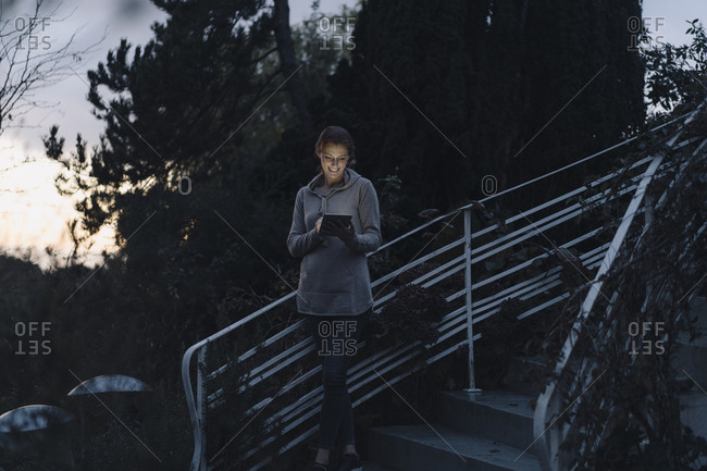 Woman using digital tablet in twilight- standing on stairs in garden