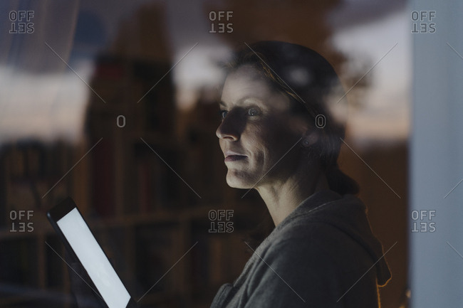 Woman looking out of window in twilight- holding digital tablet