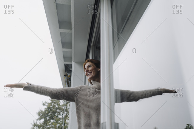 Woman checking weather- holding hand out of window
