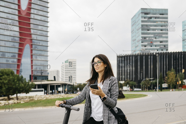 Young businesswoman using smartphone standing on e-scooter in the city