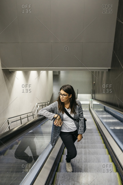 Businesswoman standing on escalator of a subway station