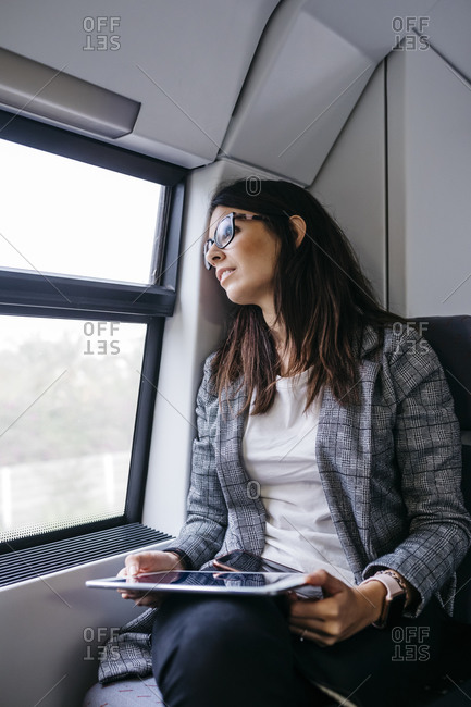 Brunette woman while traveling by train to work- with a tablet in her hands