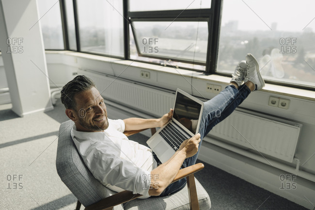 Portrait of smiling mature businessman using laptop in empty office