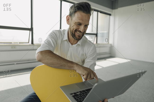 Smiling mature businessman using laptop in empty office