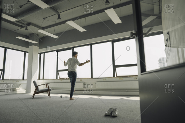 Mature businessman practicing yoga in empty office